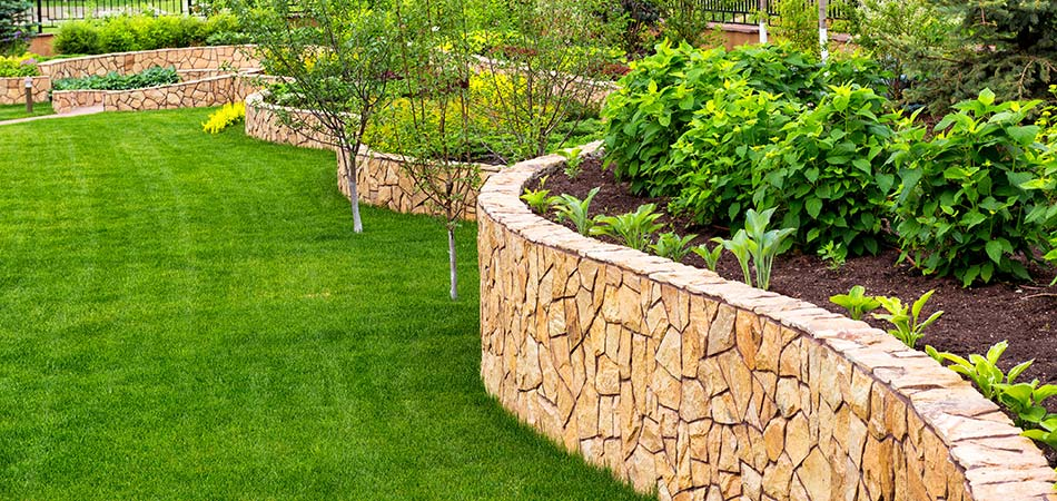 Winding retaining wall overlooking green grass with pathway.